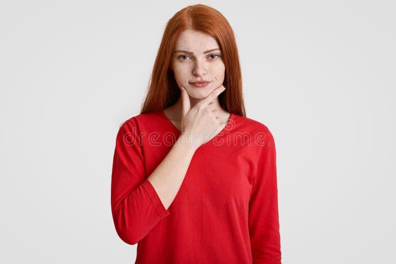 La taille vers le haut du portrait de la femelle rusée sérieuse tient le menton, fait habiller la peau de taches de rousseur, dan photos libres de droits