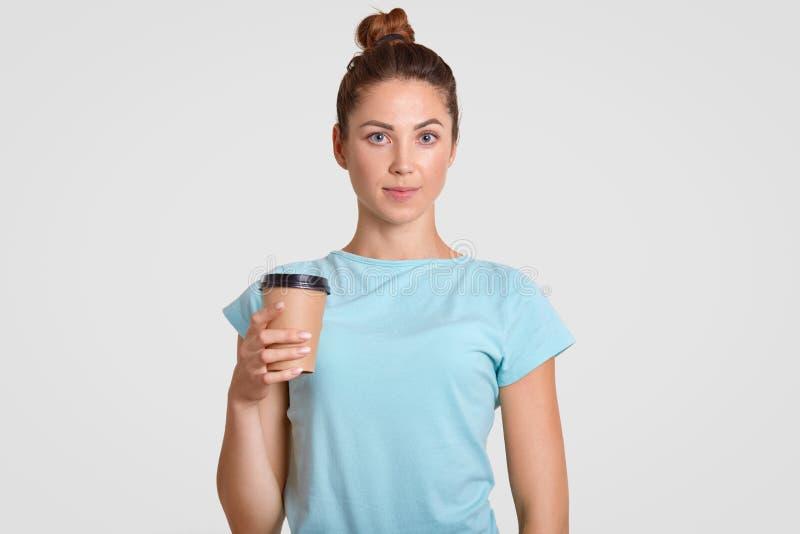 La taille vers le haut du portrait de la femme agréable à regarder avec le petit pain de cheveux, habillé dans le T-shirt bleu-cl photographie stock