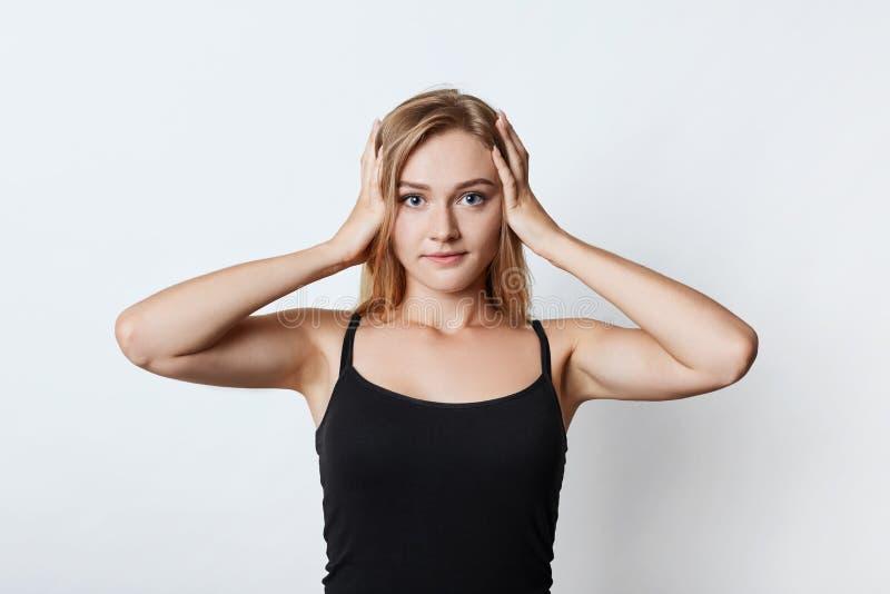 La taille vers le haut du portrait de la jolie fille a le mal de tête après que bruyant font la fête, gardent des mains sur la tê images libres de droits