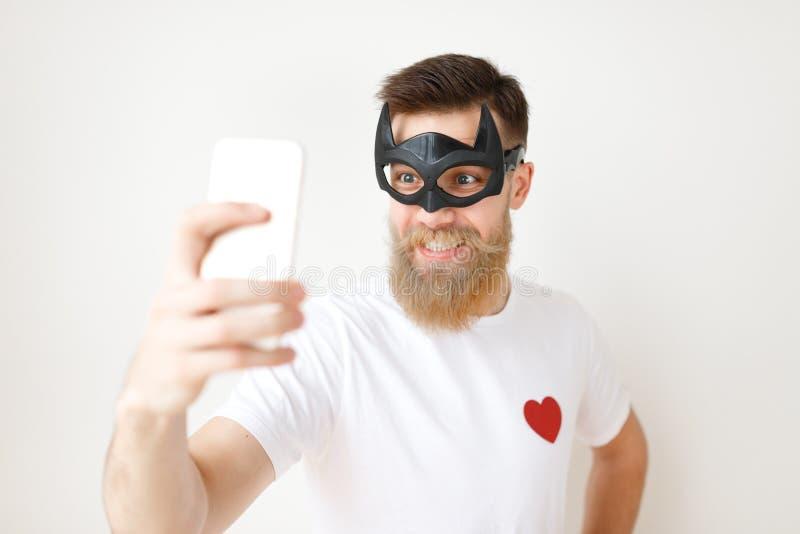 La taille vers le haut du portrait du modèle masculin barbu gai pose à l'appareil-photo futé de téléphone, utilise le masque de c photos libres de droits