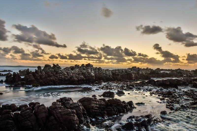 La tarde imponente tiró de rocas y de ondas de fractura en el ` s de Cabo Agulhas, de Suráfrica y por lo tanto el punto más situa fotografía de archivo libre de regalías