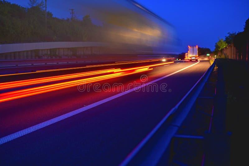 La tarde tiró de los camiones que hacían el transporte y la logística en una carretera Tráfico de la carretera - indique el camió fotografía de archivo