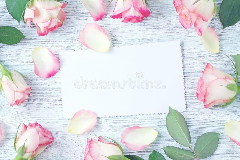 La tarjeta blanca en blanco adornó con las flores color de rosa rosadas frescas, visión superior imágenes de archivo libres de regalías