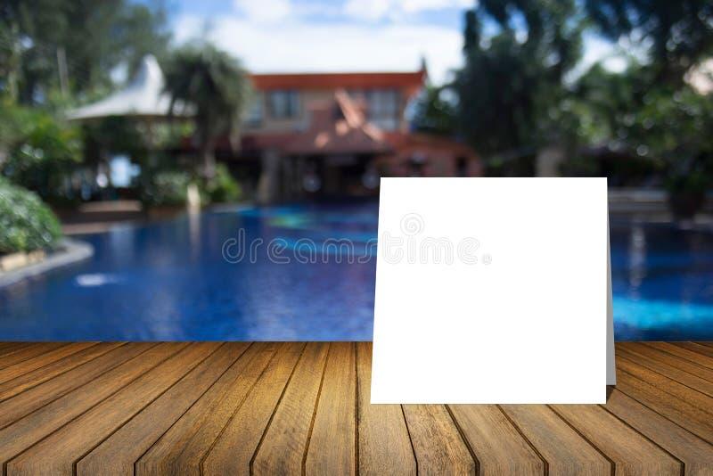 La tarjeta blanca puso el escritorio de madera o el piso de madera en piscina borrosa en el fondo del centro turístico uso para e fotos de archivo libres de regalías