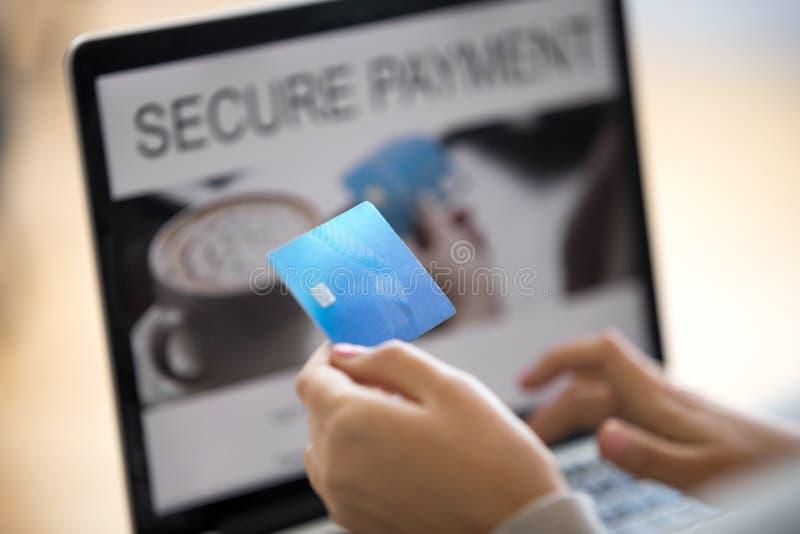 La tarjeta de crédito femenina del primer que se sostiene entra datos personales en ordenador fotos de archivo