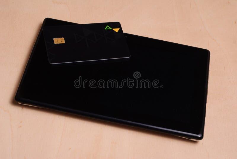La tarjeta de crédito negra está en una tableta electrónica negra, foto de archivo