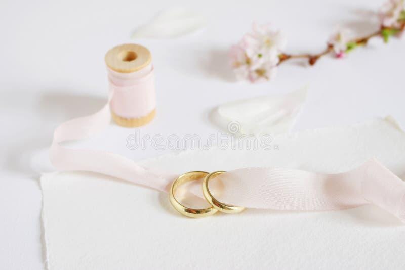 La tarjeta de felicitación de la boda, invitación con dos anillos de oro, cerezo florece, los pétalos color de rosa blancos, carr foto de archivo libre de regalías