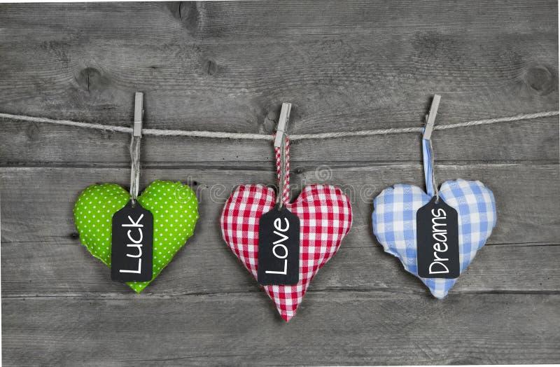 La tarjeta de felicitación con tres corazones y los buenos deseos mandan un SMS para el birthda imagen de archivo libre de regalías