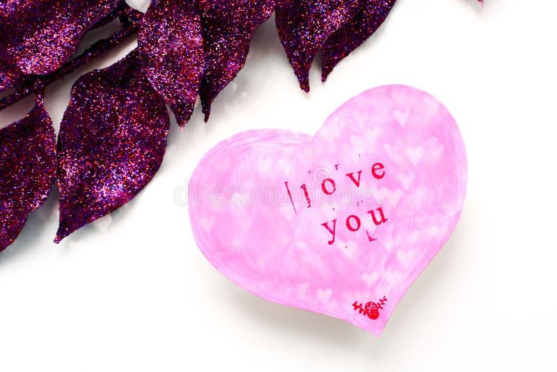 La tarjeta de felicitación del día de tarjeta del día de San Valentín en la forma de un corazón rosado con una inscripción le ama foto de archivo libre de regalías