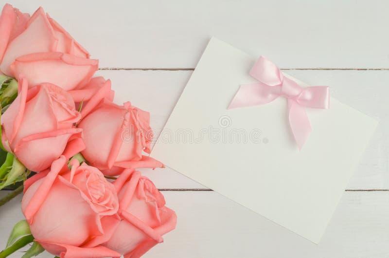 La tarjeta de felicitación en blanco con el arco de la cinta y la rosa rosados del rosa florece foto de archivo libre de regalías