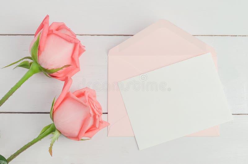 La tarjeta de felicitación en blanco con la rosa rosada del sobre y del rosa florece imagenes de archivo