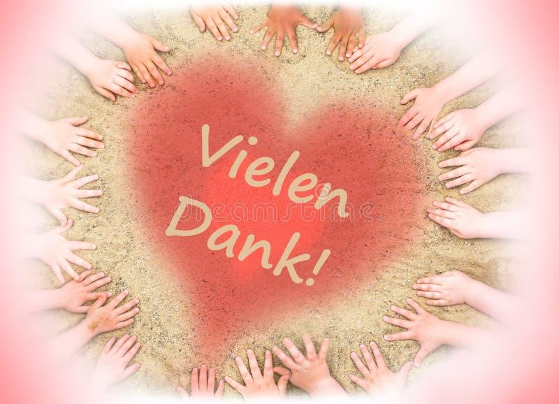 La tarjeta de felicitación de las manos de los niños y un corazón con las palabras alemanas le agradecen foto de archivo