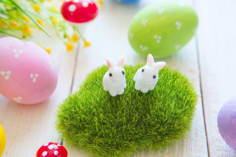 La tarjeta de felicitación de Pascua con las flores, conejito de los conejos de pascua juega y eggs en el tablón de madera blanco fotografía de archivo libre de regalías