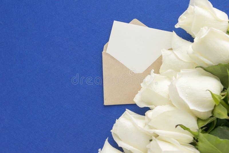 La tarjeta de felicitación vacía en sobre abierto con la rosa del blanco florece en fondo azul Opinión de ángulo superior Invitac imagen de archivo libre de regalías
