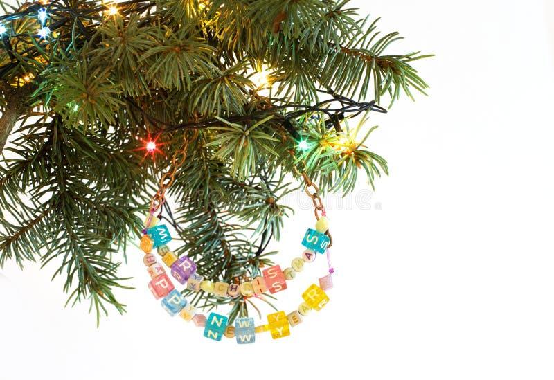 La tarjeta de la Feliz Año Nuevo y de la Feliz Navidad goteó la guirnalda de la letra en brunch del árbol de abeto imagenes de archivo