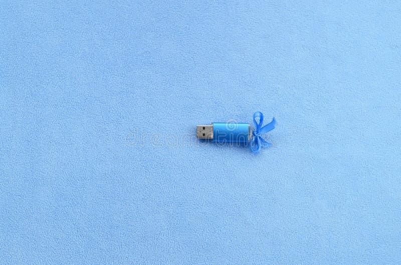 La tarjeta de memoria Flash brillante del usb del azul con un arco azul miente en una manta de la tela azul clara suave y peluda  imágenes de archivo libres de regalías