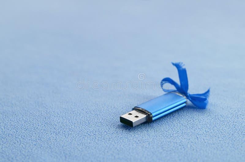 La tarjeta de memoria Flash brillante del usb del azul con un arco azul miente en una manta de la tela azul clara suave y peluda  imagenes de archivo