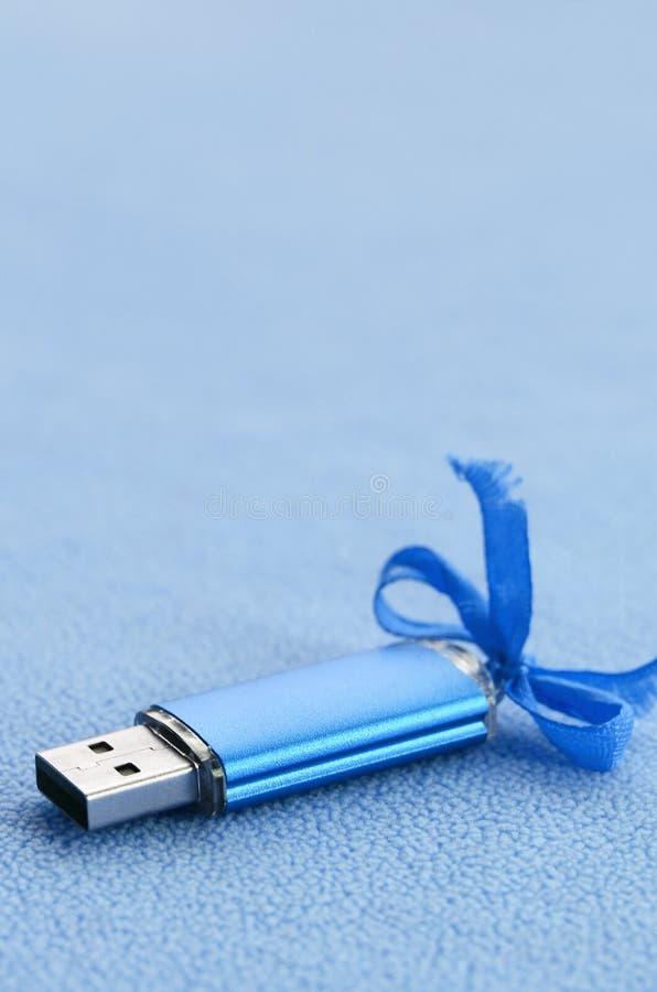 La tarjeta de memoria Flash brillante del usb del azul con un arco azul miente en una manta de la tela azul clara suave y peluda  fotos de archivo