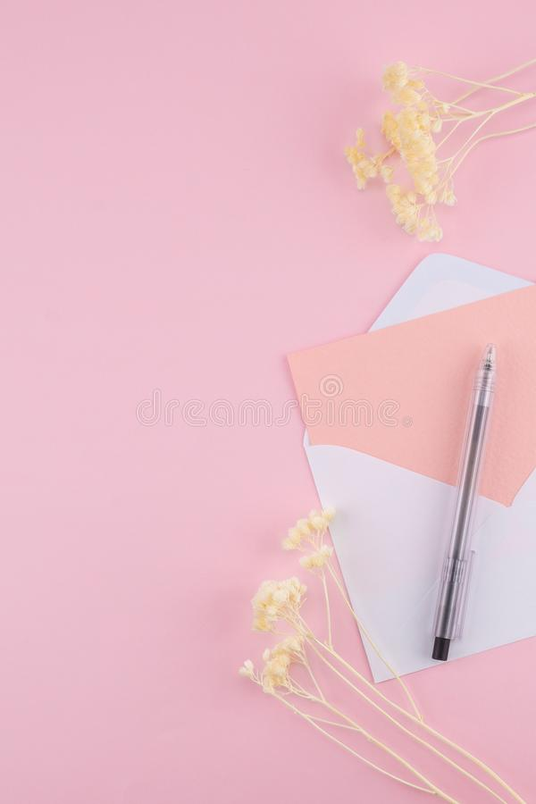 La tarjeta rosada en blanco en blanco envuelve y ennegrece la pluma foto de archivo