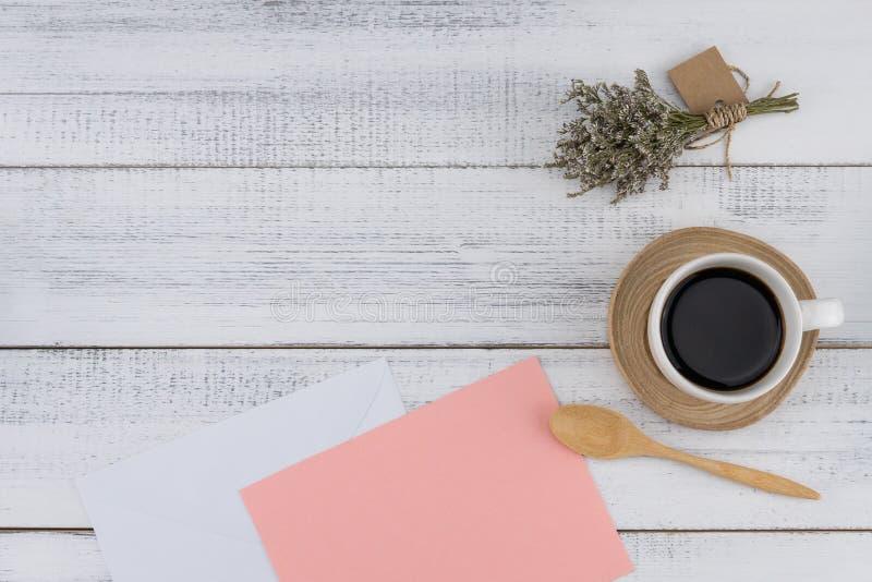 La tarjeta rosada en blanco y el blanco envuelven con una taza de café imagen de archivo libre de regalías