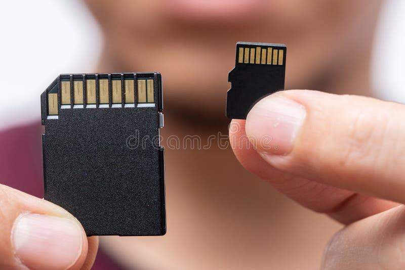 La tarjeta y el micro tarjeta SD del SD comparan en la mano masculina fotos de archivo