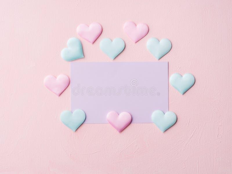 La tarjeta y los corazones en colores pastel púrpuras en rosa texturizaron el fondo imagen de archivo
