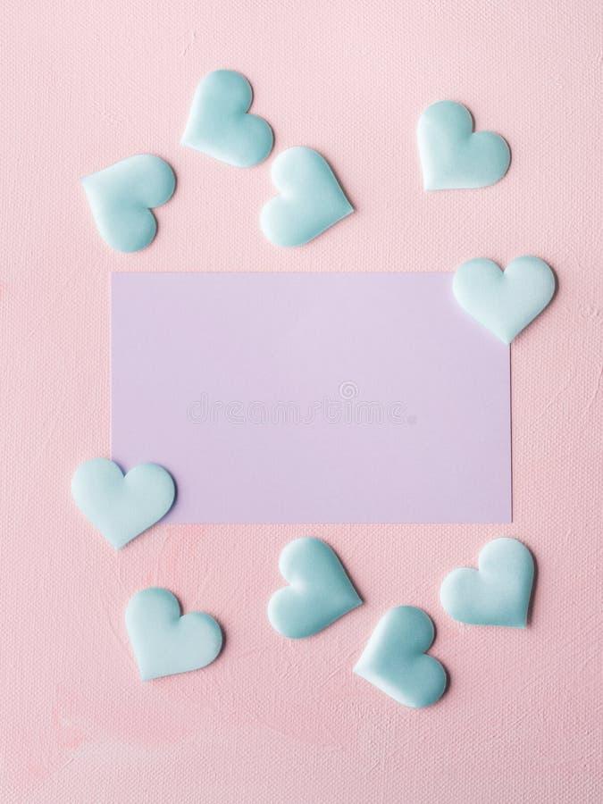 La tarjeta y los corazones en colores pastel púrpuras en rosa texturizaron el fondo fotos de archivo libres de regalías