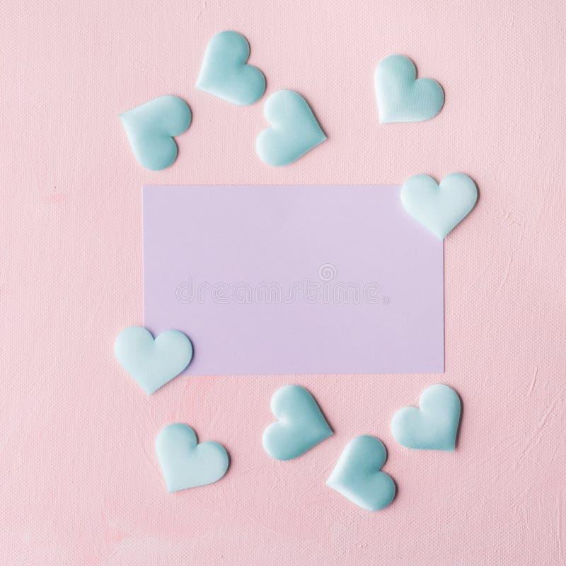 La tarjeta y los corazones en colores pastel púrpuras en rosa texturizaron el fondo imagenes de archivo