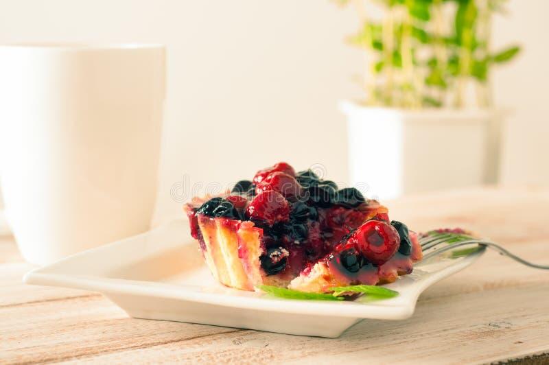 La tartelette ou le gâteau fraîche de baie a rempli de crème anglaise, de framboise, de groseille rouge de myrtille et de dessert image libre de droits