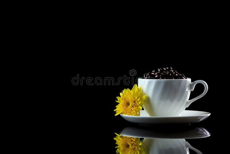 La tasse avec des grains de café et le chrysanthème jaune sur un noir se reflètent image stock