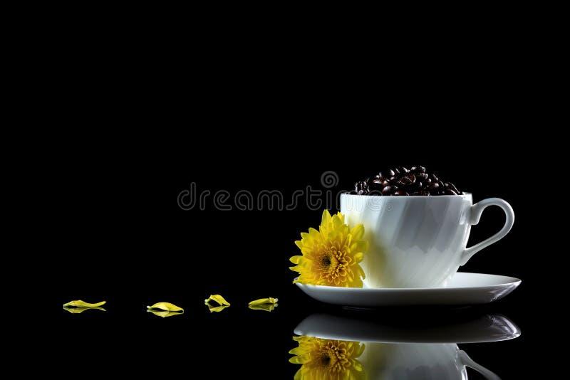 La tasse avec des grains de café et le chrysanthème jaune sur un noir se reflètent photo libre de droits