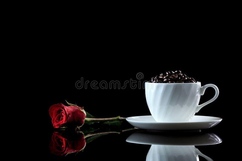 La tasse avec des grains de café et s'est levée sur un fond réfléchi noir photos libres de droits
