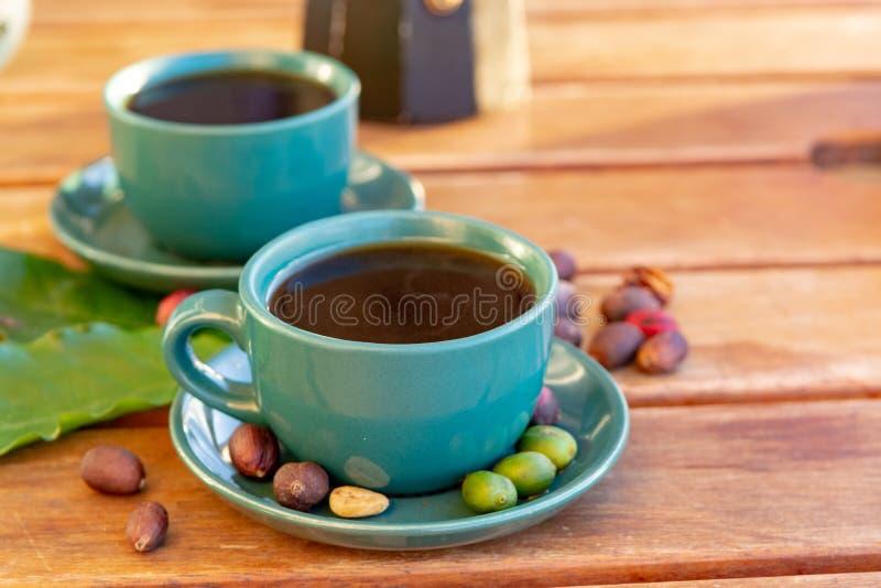 La tasse avec du café noir a servi dehors avec le vert cru, le rouge mûr et les grains de café rôtis, décorés des feuilles vertes image stock