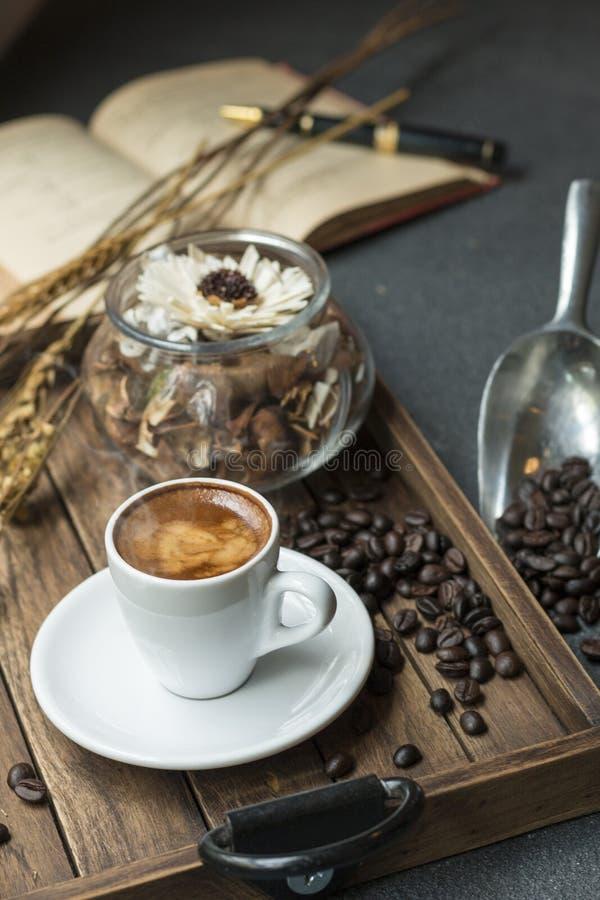 La tasse d'expresso, le grain de café, le livre et les fleurs sèches cognent sur en bois photographie stock
