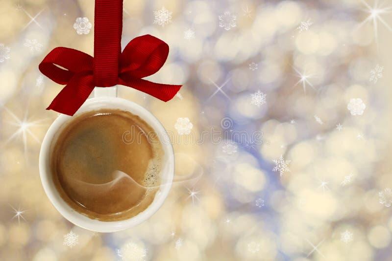 La tasse de café chaud avec de la fumée faite à partir de la boule de Noël, babiole accroche sur le ruban rouge sur le fond des l photo stock