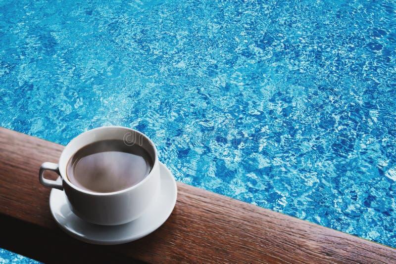La tasse de café chaud boit sur la table en bois, avec de l'eau à l'arrière-plan de piscine image stock