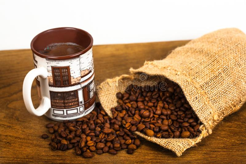 La tasse de café et les grains de café dans un sac mettent en sac photos stock