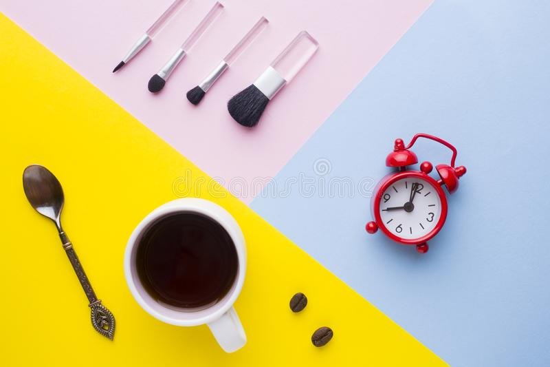 La tasse de café, observent l'horloge et les brosses de maquillage sur les milieux colorés Matin d'affaires de concept image stock
