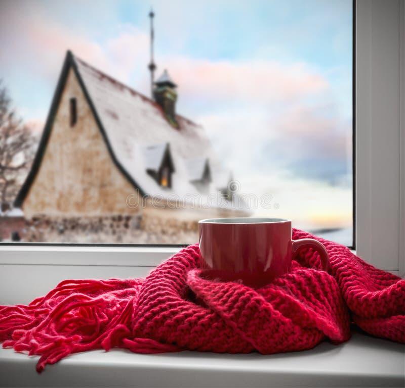 La tasse de café ou de thé chaud est enveloppée avec une écharpe sur le rebord de fenêtre images libres de droits