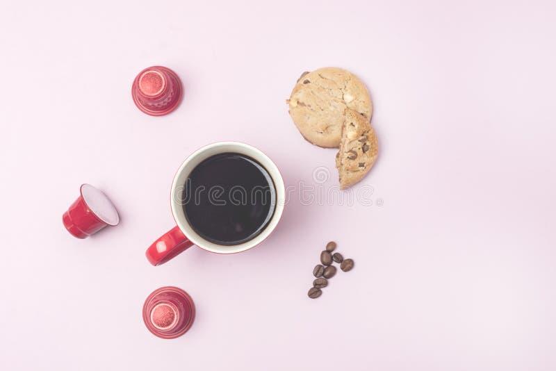 La tasse de café rouge avec du café rouge capsule la vue supérieure étendue par appartement de biscuits de grains de café de l'es photos libres de droits