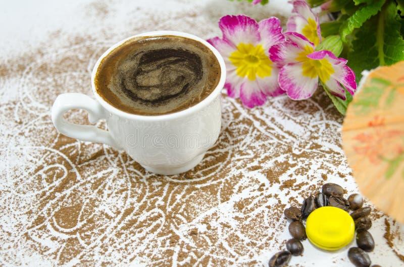 La tasse de café sur un cacao a arrosé la table photographie stock libre de droits