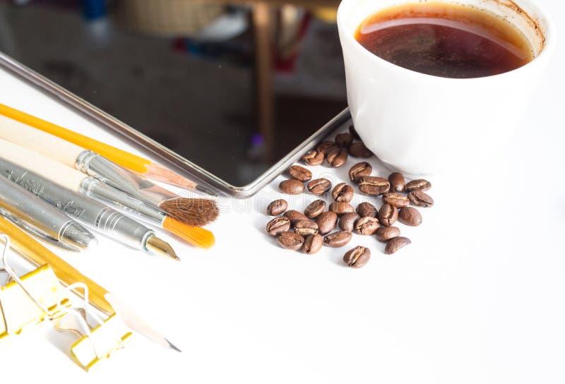 La tasse de comprimé de composition de stylos de café balaye des crayons sur b blanc images libres de droits