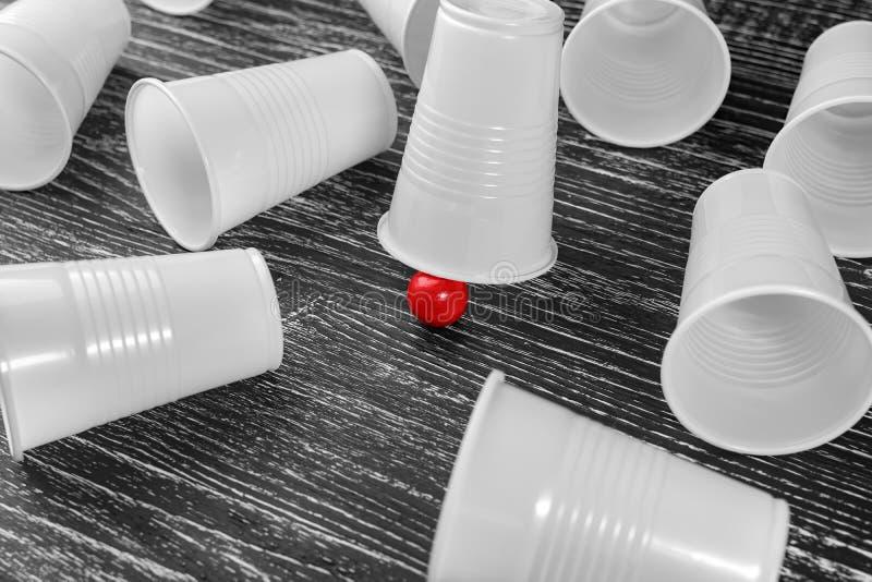 La tasse de gain dans l'escroquerie avec une boule rouge professionnelle photo libre de droits