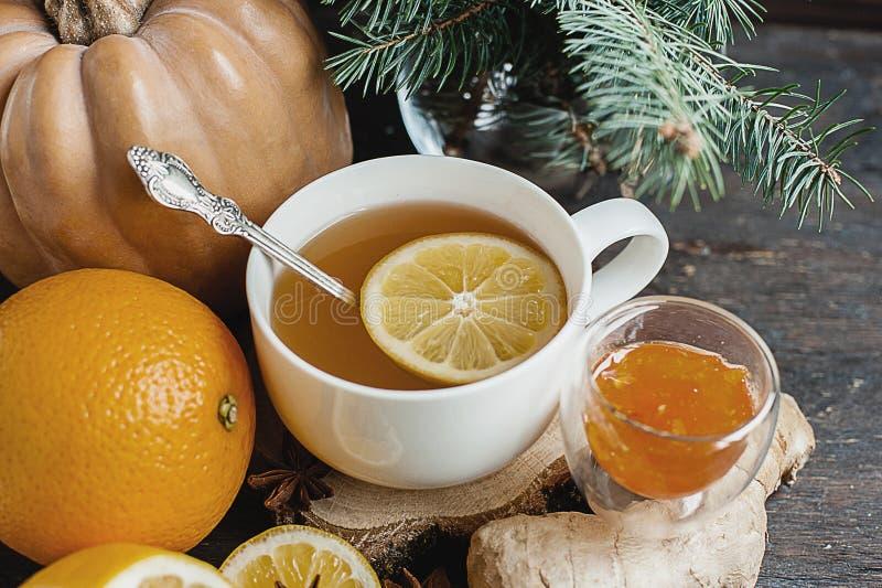 La tasse de thé chaud de citron avec le potiron orange et le gingembre bloquent sur un fond en bois Froid sain de boissons Boisso image libre de droits