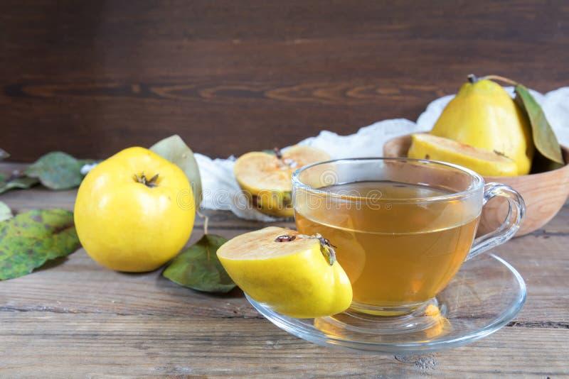 La tasse de thé chaud et le coing frais portent des fruits sur la table photo stock