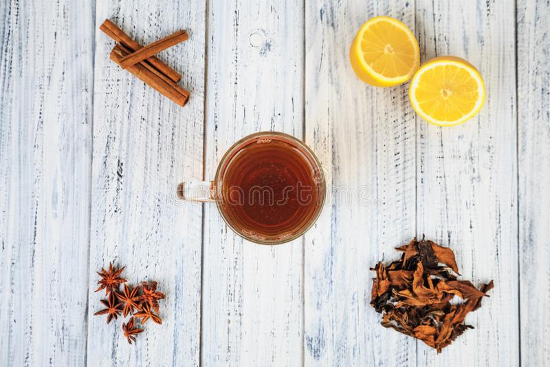 La tasse de thé, citron, cannelle, clous de girofle, a séché des feuilles de thé photo stock