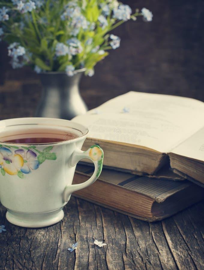 La tasse de thé, de livres de vintage et d'été fleurit sur la table photographie stock libre de droits