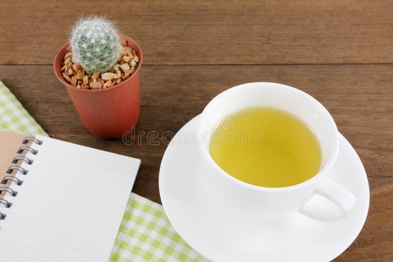 La tasse du thé vert japonais et de peu de cactus dans le pot d'usine et le petit carnet avec le tissu de coton vert photos libres de droits