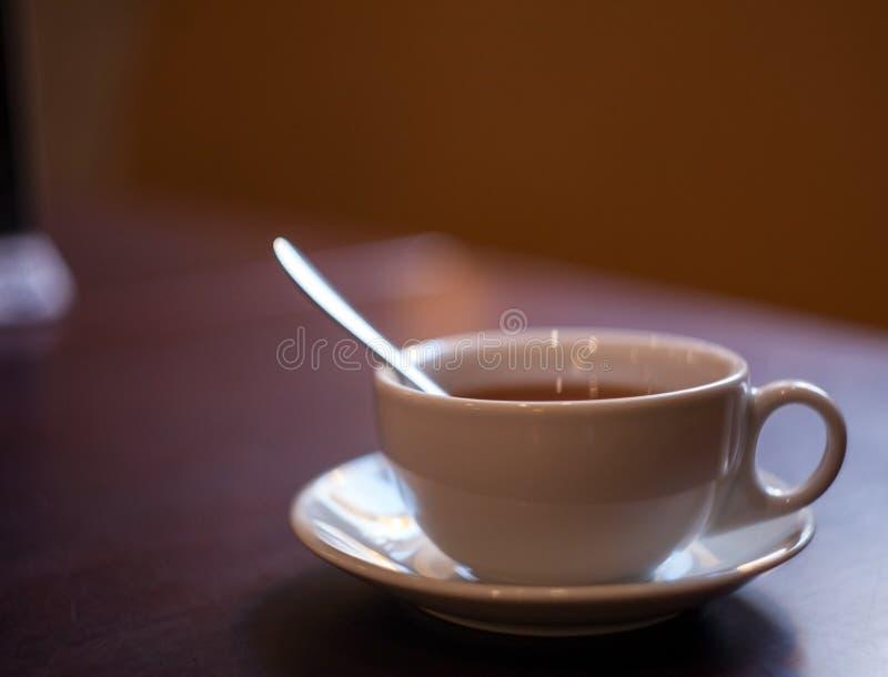 La tasse en céramique avec le thé et une cuillère sur une obscurité ont brouillé le fond images stock