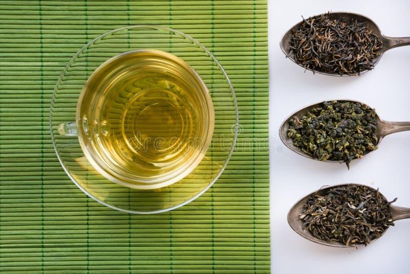 La tasse en verre de thé vert geen dessus des serviettes et trois cuillères avec le genre de varios de thé photos stock
